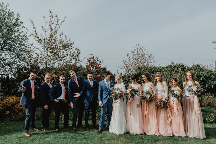 Wedding Party Portrait with Bridesmaids in Peach and White Separates, Bride in Lace Wedding Dress and Groom in Navy Blue Suits