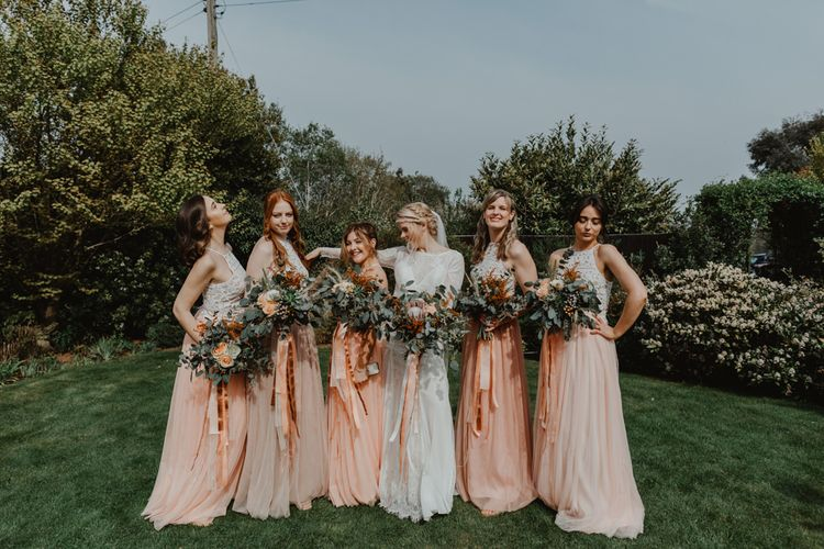 Bridal Party Portrait with Bridesmaids in Peach and White Separates and Bride in Lace Wedding Dress with Long Sleeves
