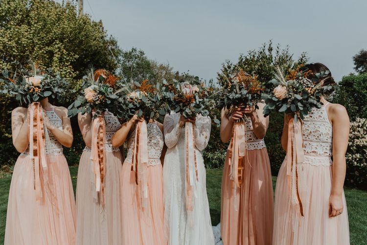 Bridal Party Portrait with Bridesmaids in Peach and White Separates and Bride in Lace Wedding Dress  Holding up Their Wedding Bouquets