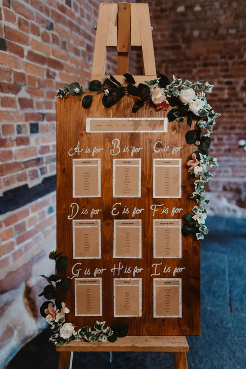 Wooden Table Plan on an Easel with Rose Wedding Decor
