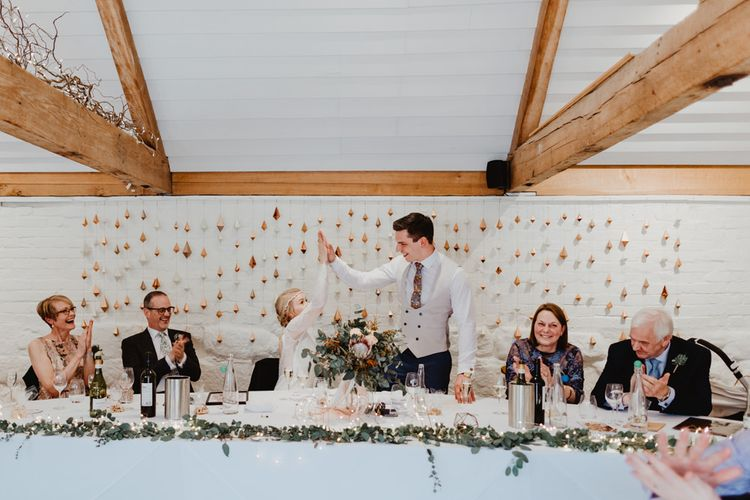Bride and Groom Having a High Five at the Top Table with Geometric Backdrop