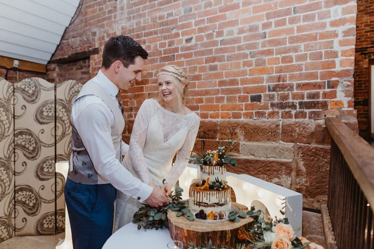 Bride in Lace Allure Bridals Wedding Dress with Long Sleeves and Groom Cutting the Drip Wedding Cake