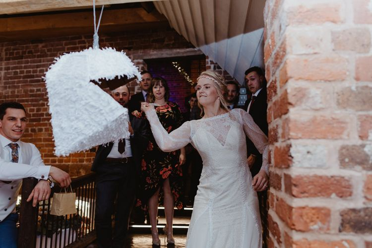 Bride in Lace Allure Bridals Wedding Dress with Long Sleeves Hitting the Piñata