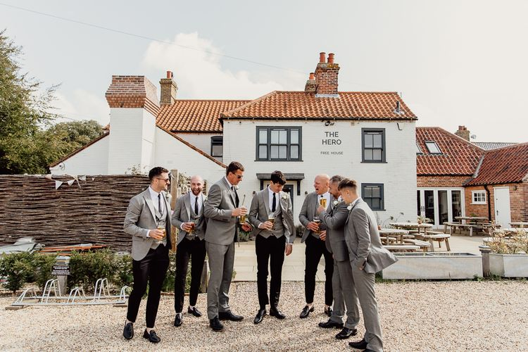 Groom and groomsmen toast the celebration at Norfolk barn wedding