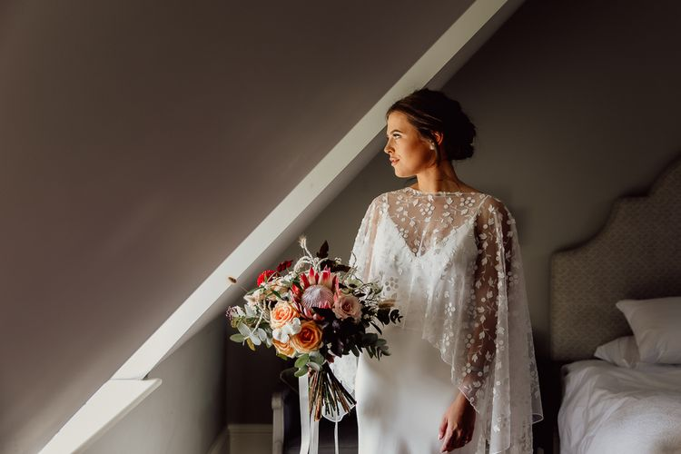 Bridal cape in lace over minimalist wedding dress with blush bouquet