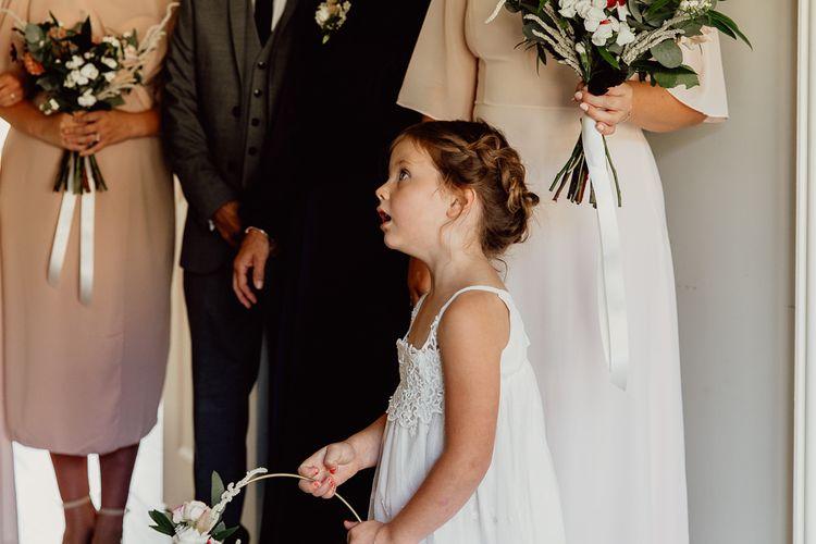 Flower girl in white dress at Norfolk barn wedding