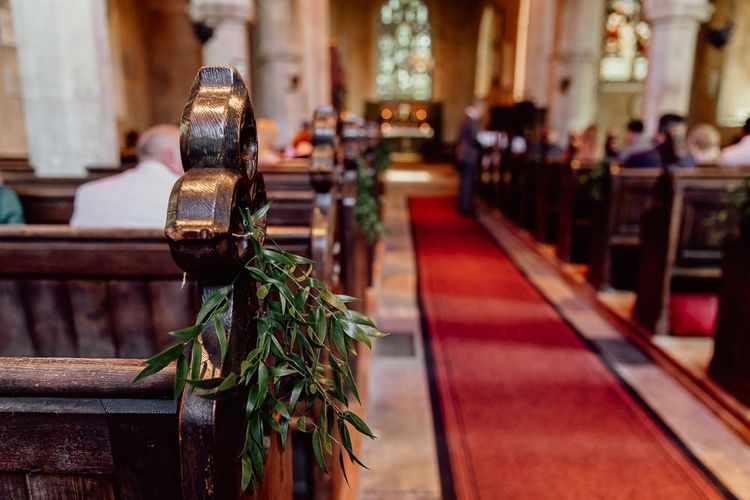 Church wedding ceremony with aisle decor before Norfolk barn wedding reception