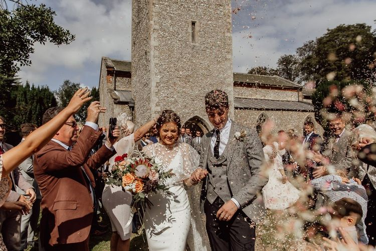 Confetti exit for bride and groom after church ceremony