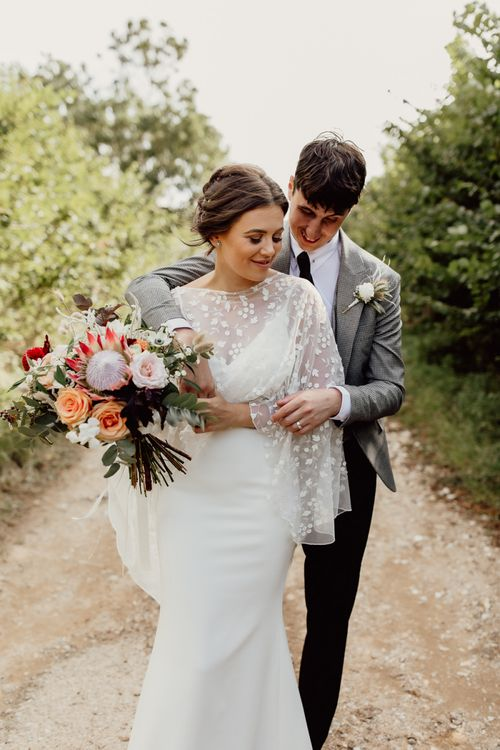 Bride in lace cover-up with pink and coral bouquet