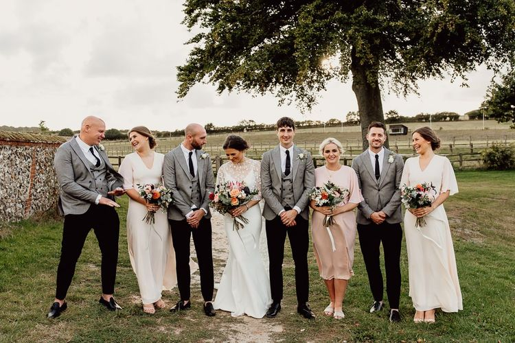 Bridal party in pink dresses with groomsmen in grey suits