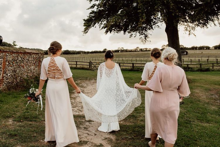 Blush bridesmaid dresses with lace bridal cape