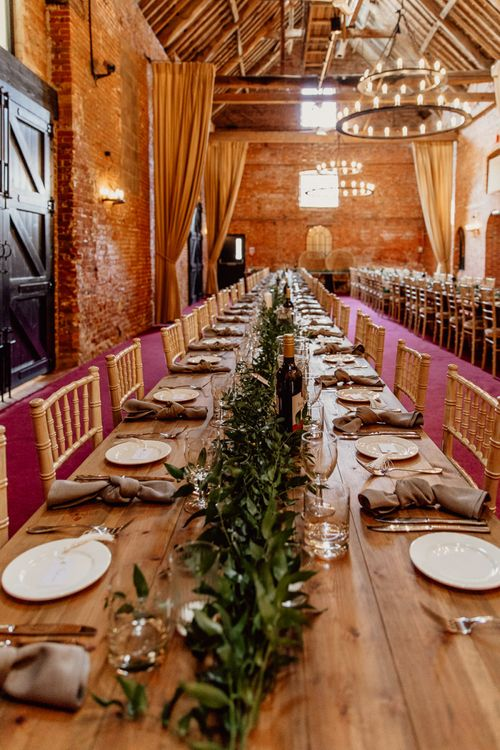 Foliage and candles on trestle tables at Norfolk  barn wedding miChris-53