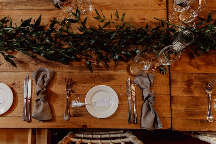 Foliage and candles on trestle tables at Norfolk barn wedding