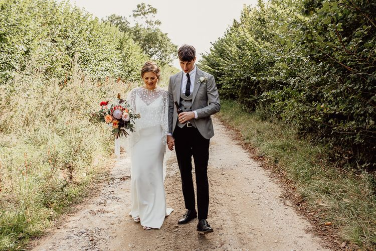 Bride and groom walk through grounds of Norfolk barn wedding venue