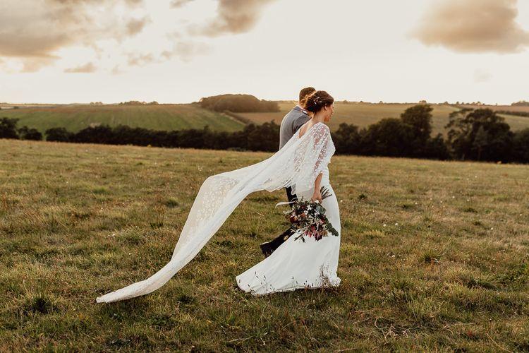 Lace bridal cape over minimalist Sassi Holford wedding dress