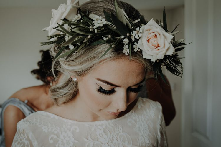 Bride wearing lace bridal top and white floral crown for relaxed country wedding with festival styling