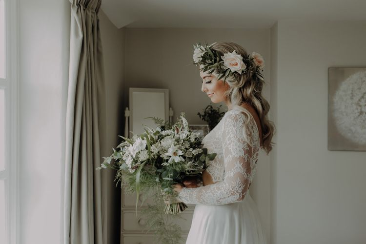 Bride wearing flower headpiece and holding white floral bouquet