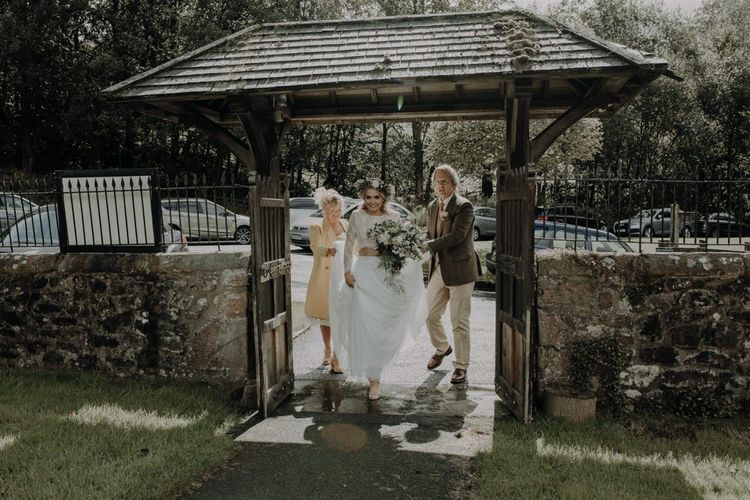 Bride arriving at the church with her family wearing two piece bridal gown