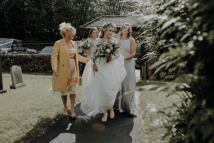 Bride wearing floral crown and white floral bouquet with her bridesmaids in silver Ghost dresses