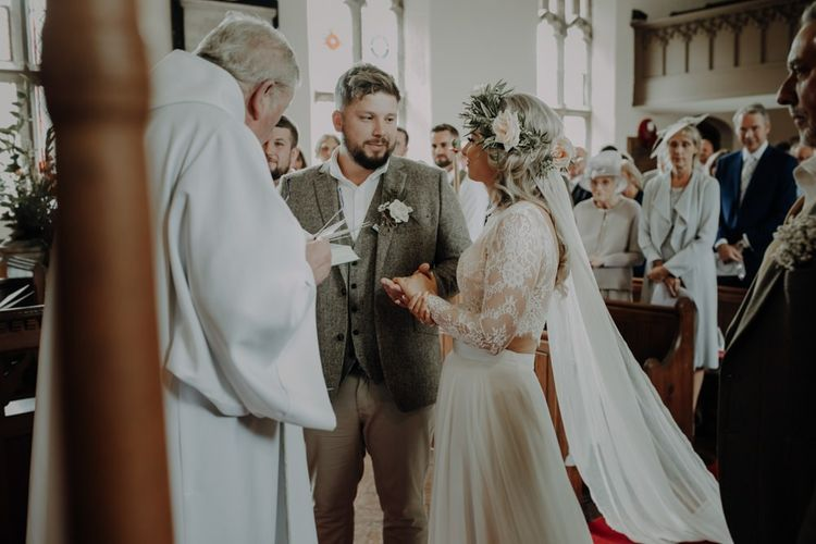 Bride wearing two piece bridal dress and groom in relaxed suit with floral button hole