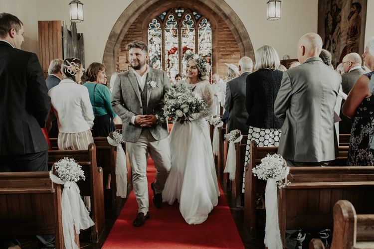 Bride and groom tie the knot at church ceremony wearing two piece bridal dress and white floral bouquet
