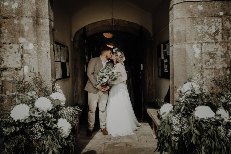 Bride and groom kiss at the church entrance with white floral decor