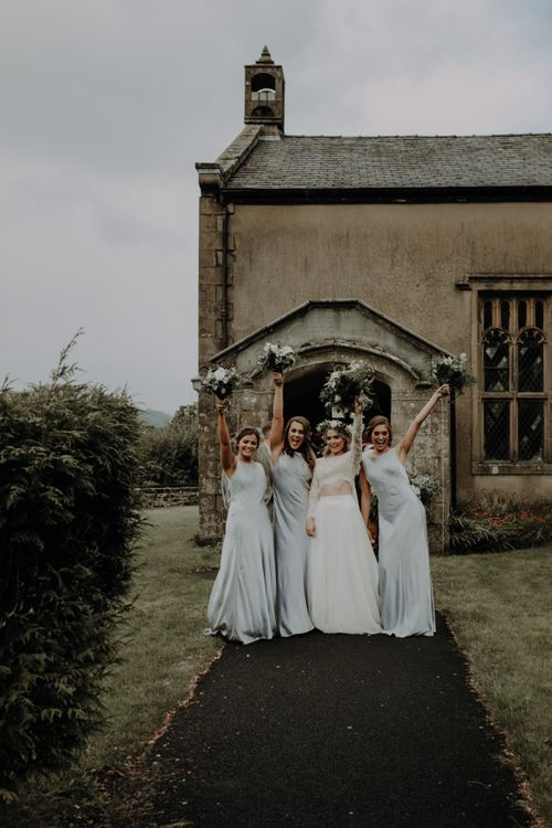 Bride and her bridesmaids with white floral bouquets at church ceremony