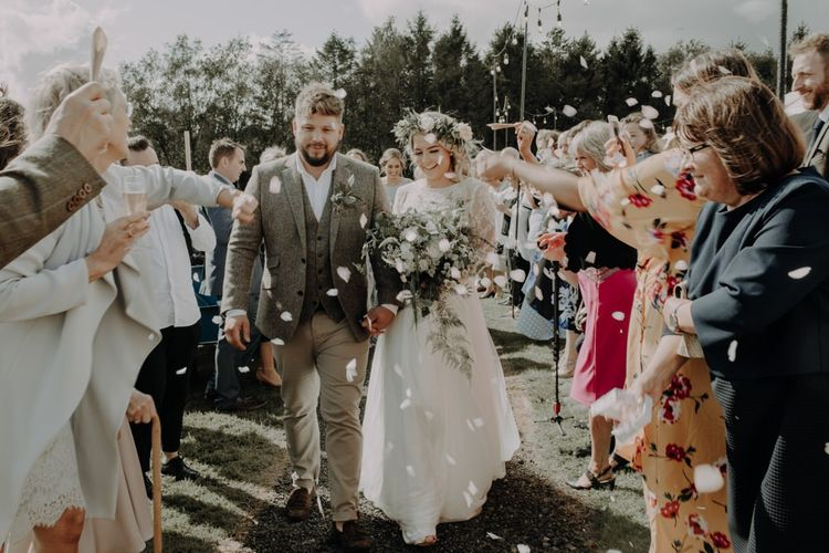 Bride and groom confetti shot wearing white flower crown at Hobbit Hill