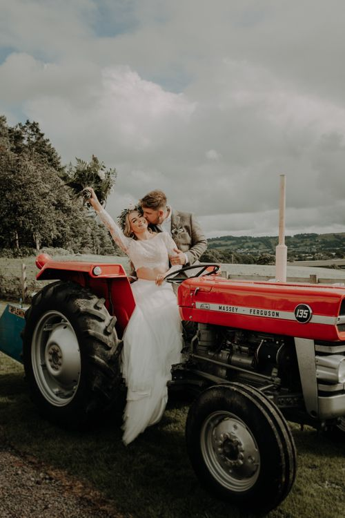 Bride and groom pose on a red tractor at relaxed country wedding