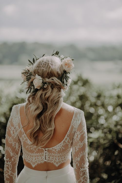 Back of brides lace two piece dress wearing white rose floral head piece
