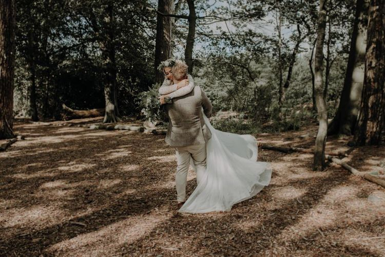 Bride and groom embrace at outdoor country wedding with festival touches