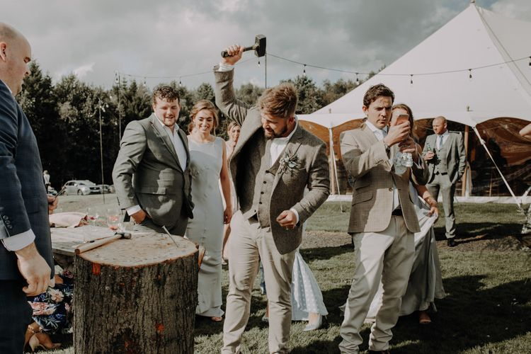 Groom playing hammershlagen at relaxed  outdoor wedding with marquee reception