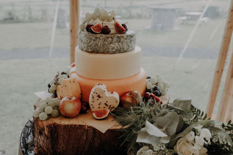 Three tier cheese wedding cake styled on rustic tree stump for relaxed country reception