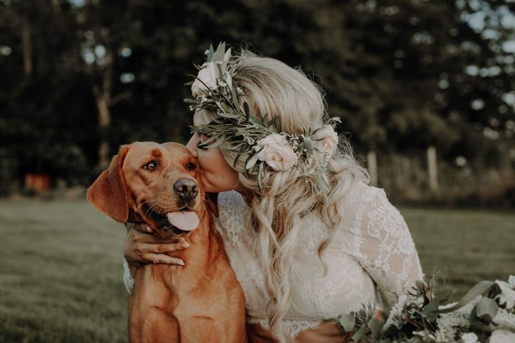 Bride wearing beautiful floral head piece enjoys a moment with her dog