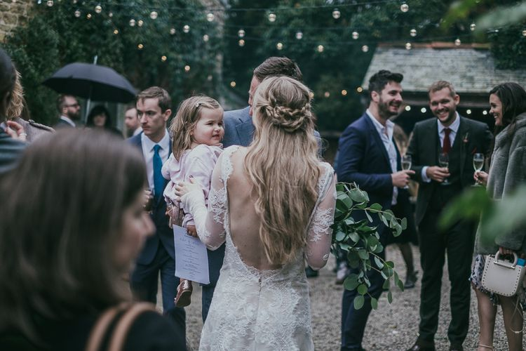 Bride in Backless Lace Wedding Dress with Braided Half Up and Half Down Wedding Hair