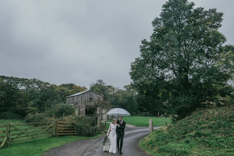 Bride and Groom Walking Through the Countryside Under Clear Umbrella