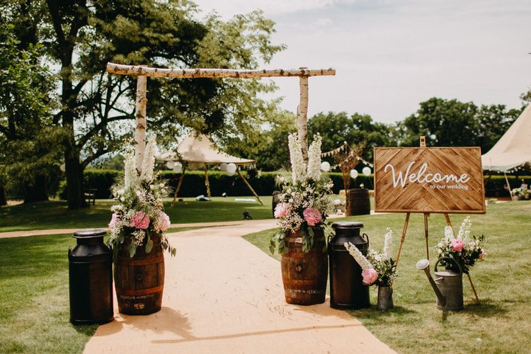 Welcome Entrance with Milk Churns, Barrels, & Wooden Arch & Sign | DIY Rustic Tipi Wedding at Riverhill Gardens, Sevenoaks | Frances Sales Photography