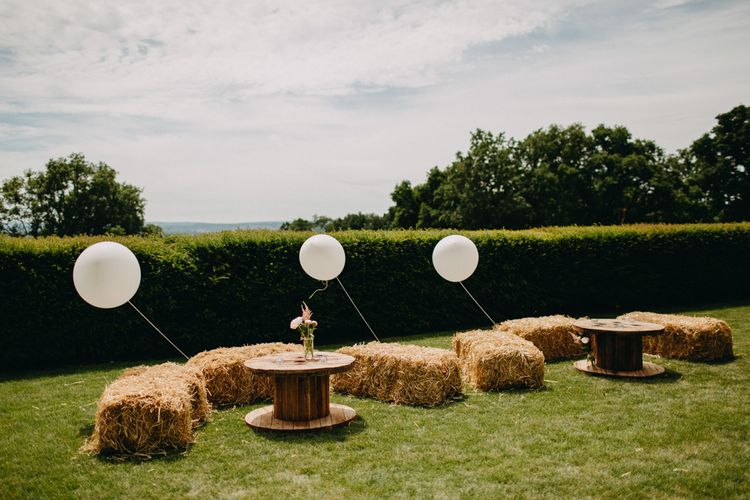 Hay Bale Seating Area with Giant Balloon Wedding Decor | DIY Rustic Tipi Wedding at Riverhill Gardens, Sevenoaks | Frances Sales Photography