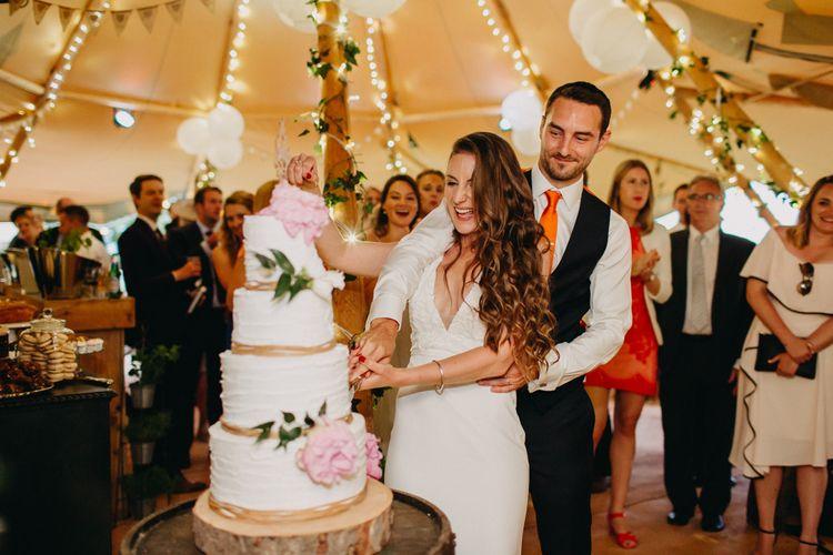 Cutting the Wedding Cake | Bride in Halo & Wren Wedding Dress | Groom in Moss Bros. Suit | DIY Rustic Tipi Wedding at Riverhill Gardens, Sevenoaks | Frances Sales Photography