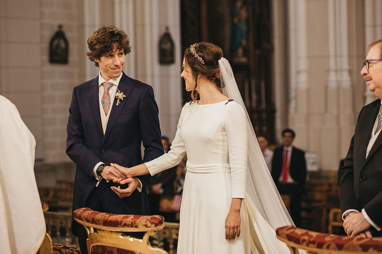 Church Wedding Ceremony with Bride in Nnavascues Embroidered Back Wedding Dress and Groom in Navy Suit Holding Hands at the  Altar