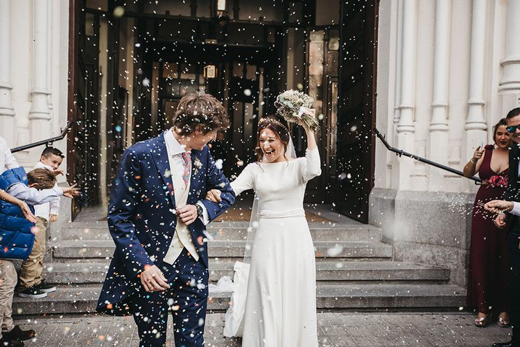 Confetti Moment with Bride in Nnavascues Embroidered Back Wedding Dress and Groom in Navy Suit