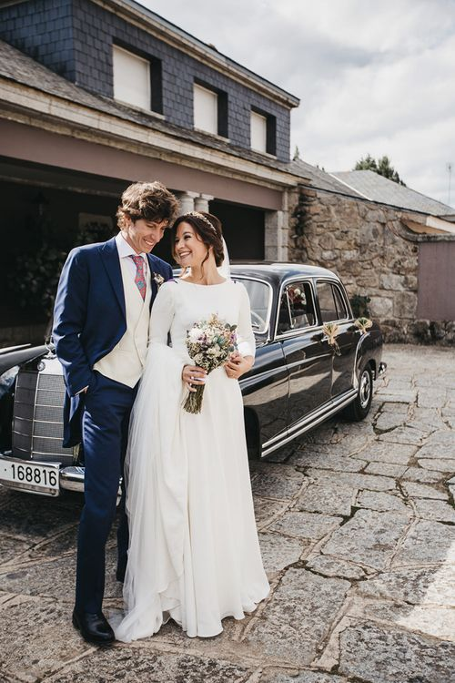 Bride in Nnavascues Embroidered Back Wedding Dress and Groom in Navy Suit Standing By Their Wedding Car