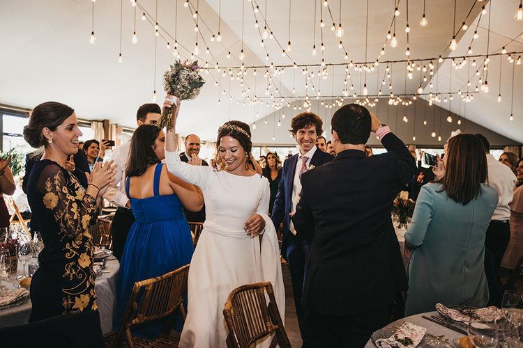 Bride in Nnavascues Embroidered Back Wedding Dress and Groom in Navy Suit Entering The Wedding Reception