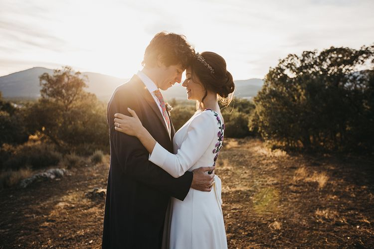 Golden Hour Portrait of Bride in Nnavascues Embroidered Back Wedding Dress and Groom in Navy Suit