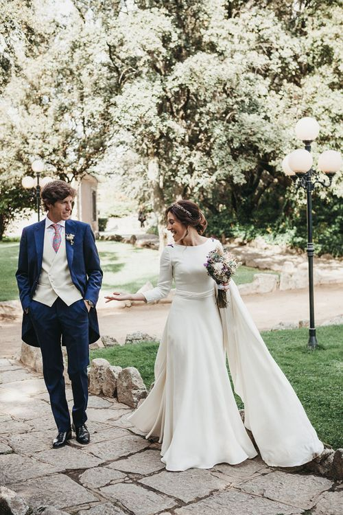 Bride in Nnavascues Embroidered Back Wedding Dress and Groom in Navy Suit