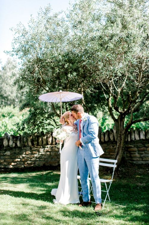 Bride in Beaded Marchesa Wedding Dress and in Groom Light Blue Suit Kissing Under a Parasol