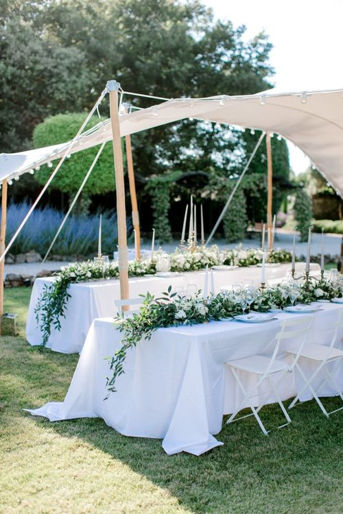 Trestle Tables with Foliage Table Runner Under a Stretch Tent Marquee