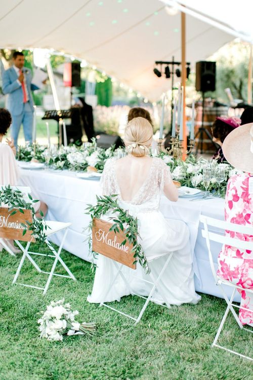 Bride with Sleek Bun Up Do Sitting at the Outdoor Reception