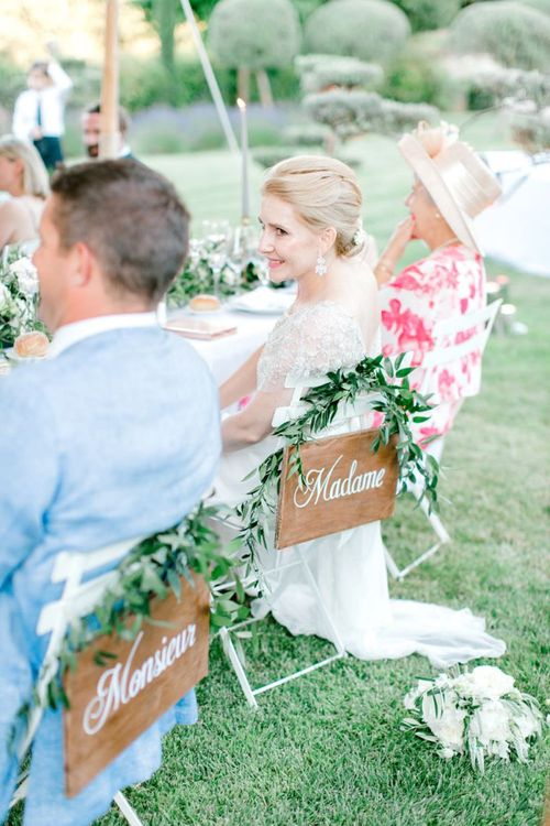 Bride and Groom Sitting at their Monsieur & Madame Reception Chairs