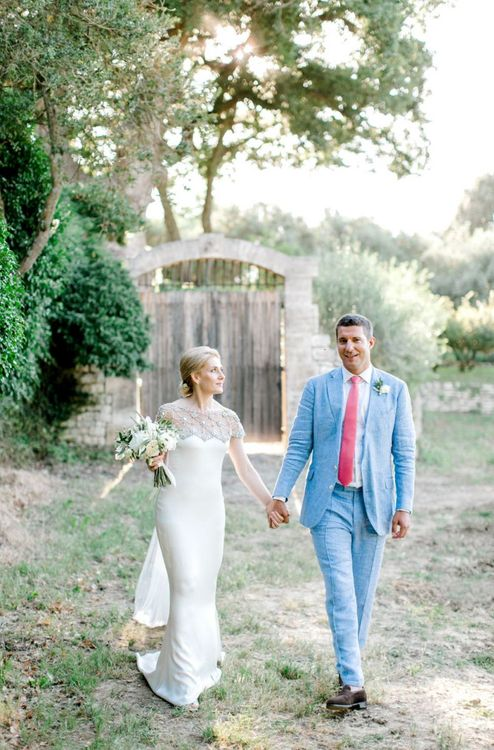 Bride in Beaded Illusion Neckline Marchesa Wedding Dress and Groom in Light Blue Suit Holding Hands